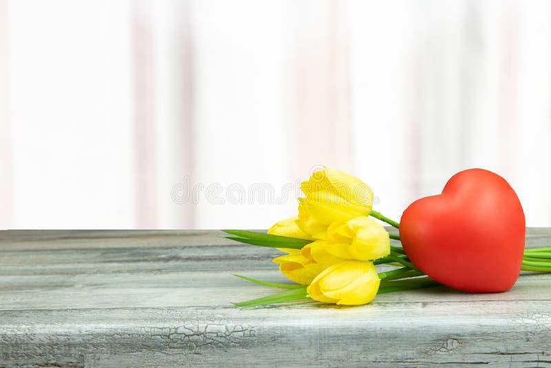 Dekorativ sammansättning av gula tulpan och en röd hjärta på rusti arkivbild