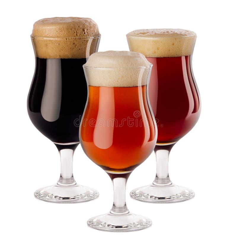 Dekorativ sammansättning av olikt öl i vinglas med skum - lager, rött öl, portvakt - som isoleras på vit bakgrund arkivfoto