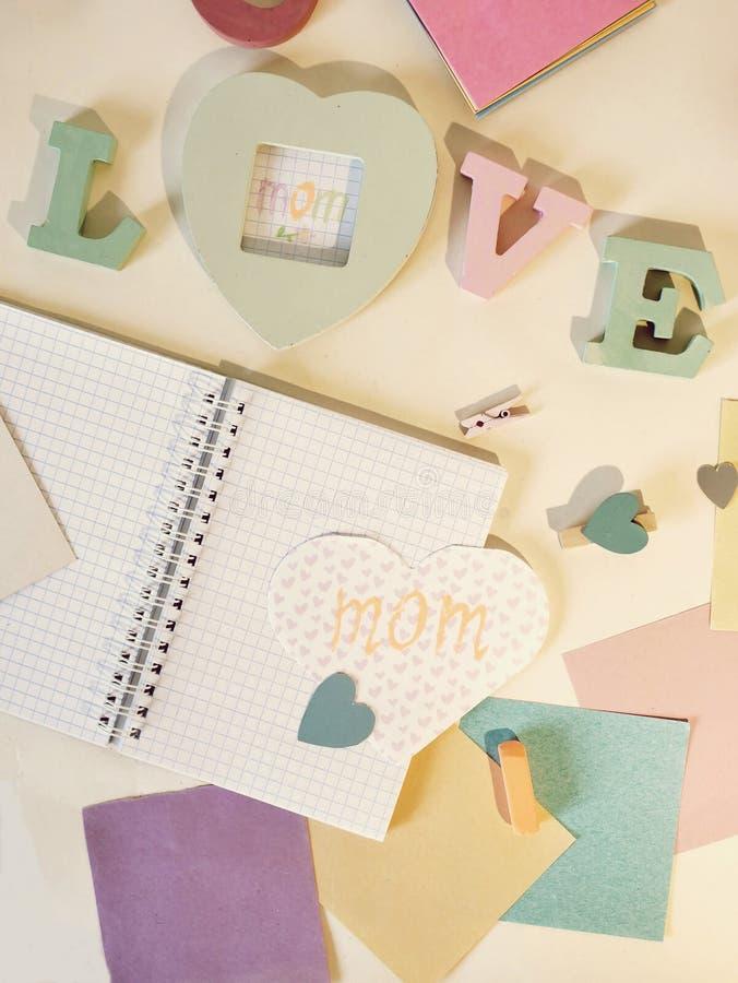 Dekorativ sammansättning för lyckönskan på mors dag, ordförälskelsen från volymetriska bokstäver, hjärtor, tomma anteckningsböcke royaltyfri foto