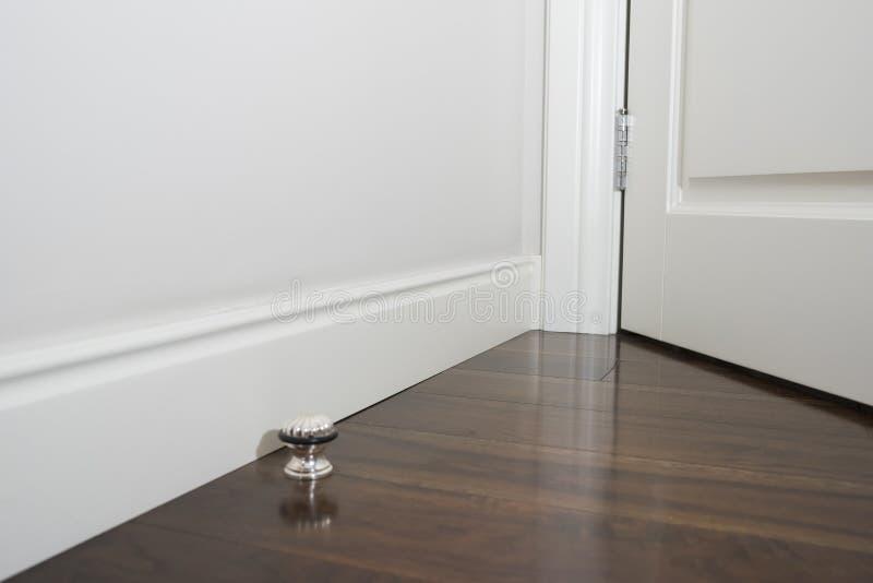 Dekorativ stöpning i hörnet av ett vitt rum med inre begrepp för mörkt trägolv h?rlig intern sikt royaltyfria bilder