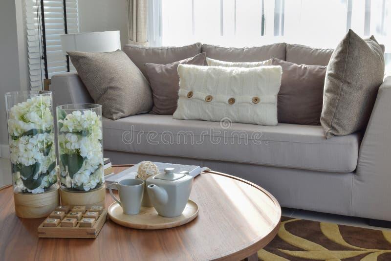 Dekorativ teservis- och exponeringsglasvas på den trärunda tabellen i vardagsrum royaltyfri bild