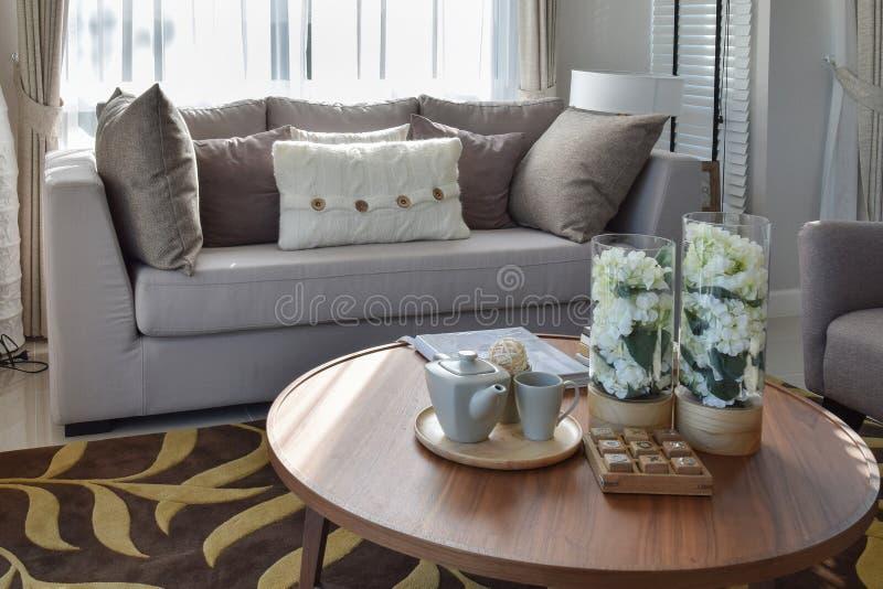 Dekorativ teservis- och exponeringsglasvas på den trärunda tabellen i vardagsrum royaltyfria foton