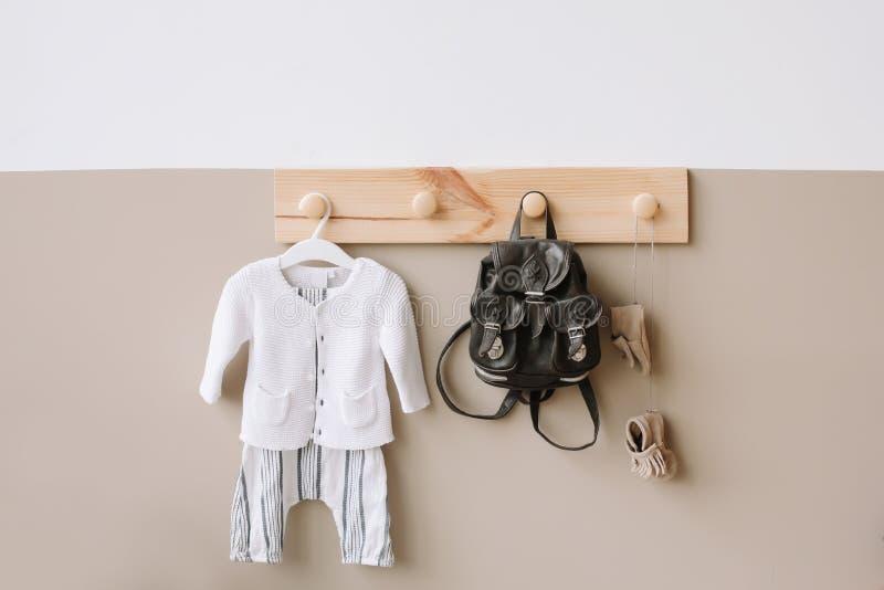 Dekorativ trähängare med den stack dräkten för påse och barns på den vita och bruna väggen arkivbilder