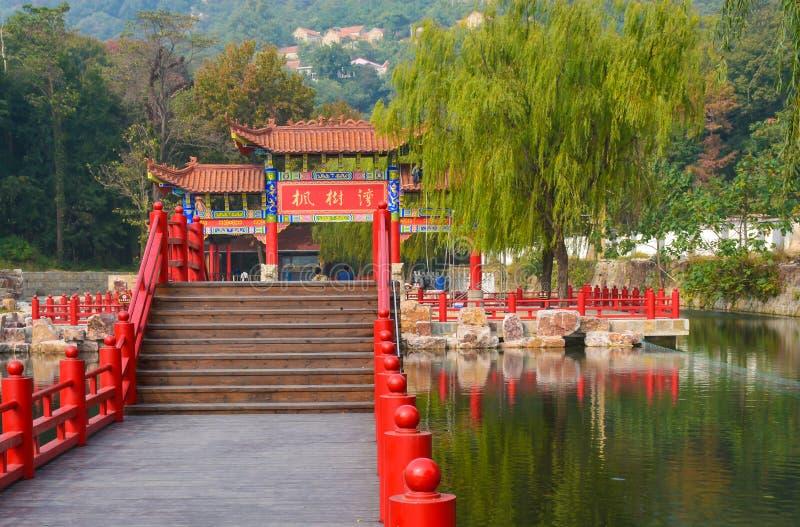 Dekorativ träkinesisk port, arkitektonisk båge på vattnet i det Jiangsu landskapet arkivfoto