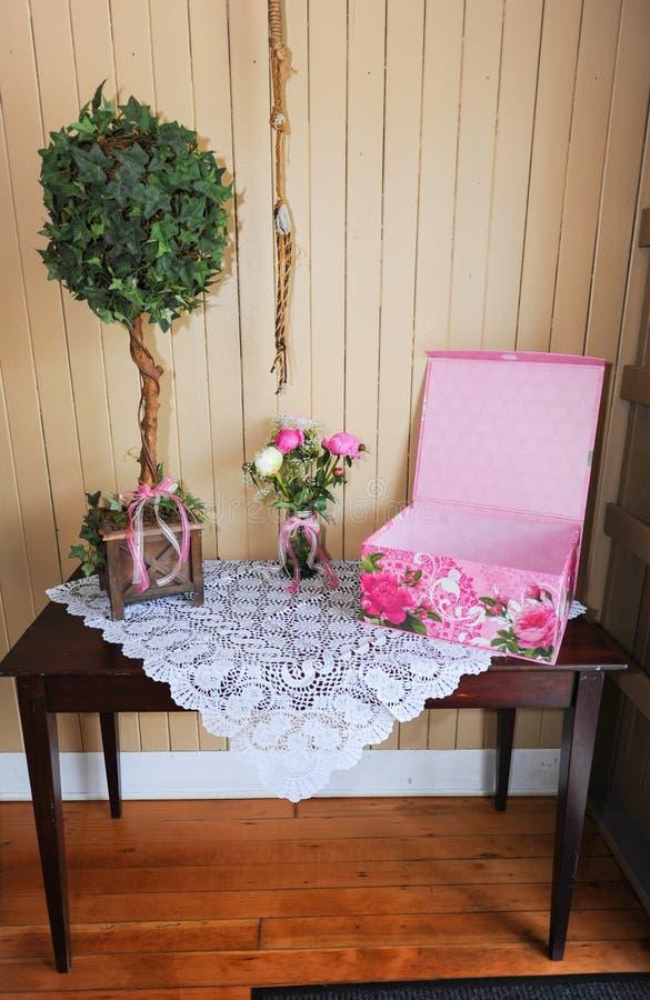 Dekorativ treen auf Tabelle mit einem rosa Kasten lizenzfreies stockbild