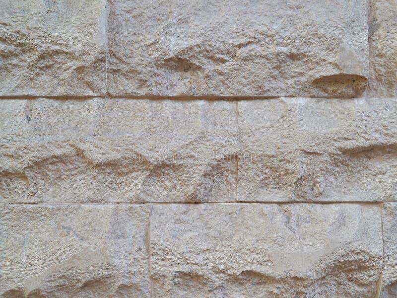 Dekorativ vägg som byggs av högg ut stentjock skiva av beige färg arkivfoto