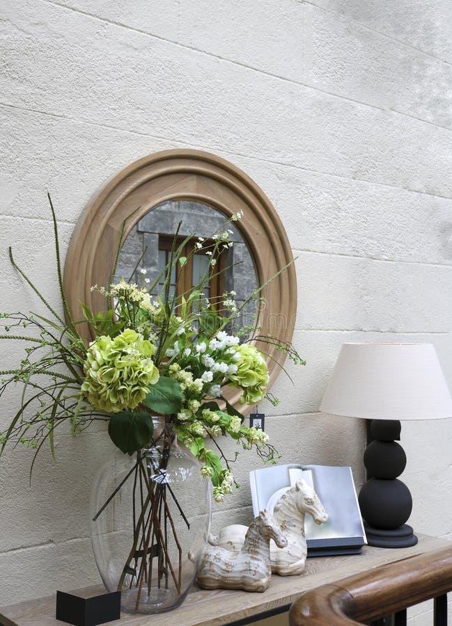 Dekorativ v?gggarnering: en spegel, en konsol med en lampa, blommor och billiga prydnadssaker royaltyfri foto