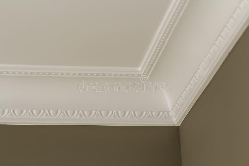 Dekorativ vit stöpningsdekor på tak av närbilddetaljen för vitt rum Inre renovering- och konstruktionsbegrepp arkivbild