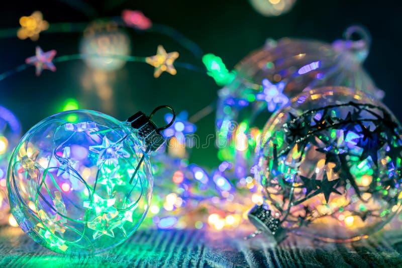 Dekorativa exponeringsglasbollar för julgran mot festlig glödande li arkivfoton