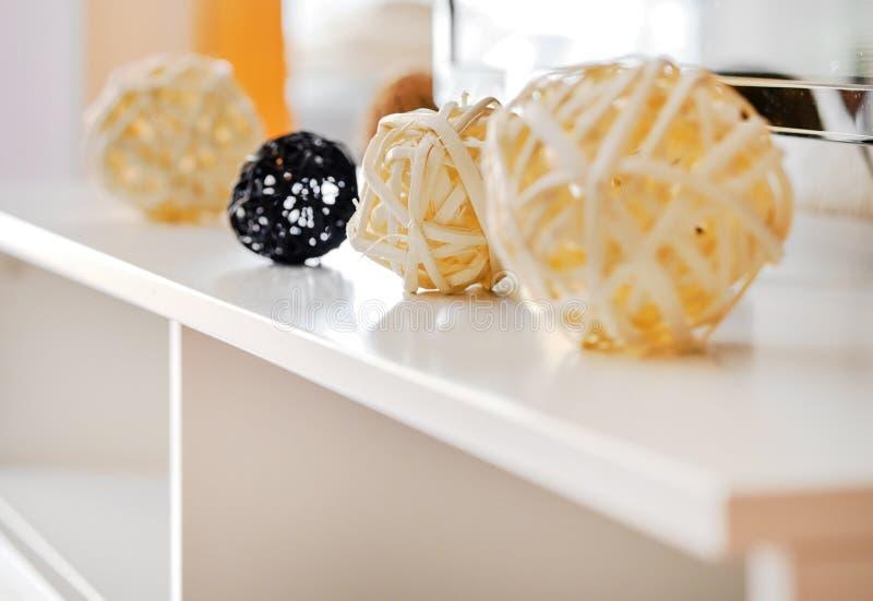 Dekorativa gula och svarta olika formbollar, gnäggar från naturliga material på en vit tabellinsida av vardagsrum, hemma arkivfoton