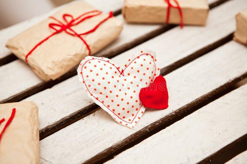 Dekorativa hjärtor och gåvaaskar på vit träbakgrund arkivfoton