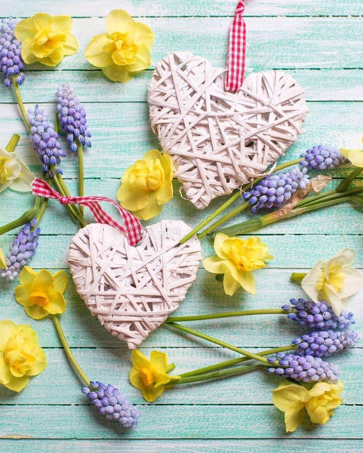 Dekorativa hjärtor och nya guling och blått fjädrar blommor på t royaltyfri foto