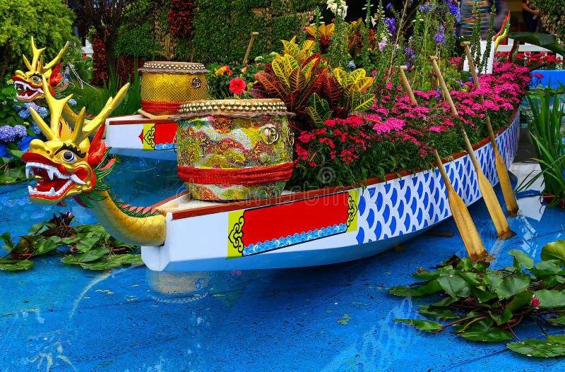 Dekorativa kinesiska drakefartyg och valsar i trädgård royaltyfria foton