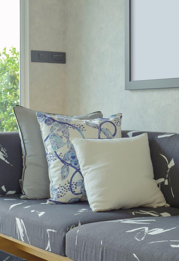 Dekorativa kuddar som ställer in på soffan med trägrunden i livi arkivbilder