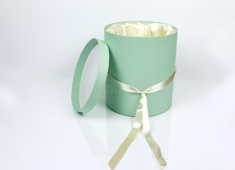 Dekorativa runda Teal Hat Box med kräm färgade det isolerade bandet royaltyfri fotografi