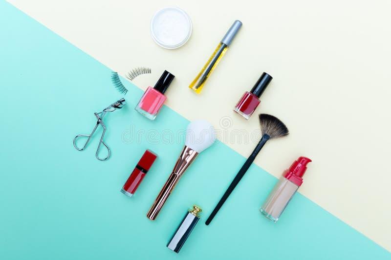 Dekorativa skönhetsmedel, makeupprodukter och borstar på pastellfärgad blå färgbakgrund royaltyfria foton