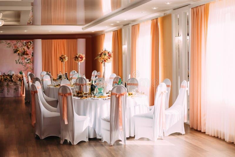 Dekorativa vitansvar och kulöra band på stolar på den festliga tabellen royaltyfri foto