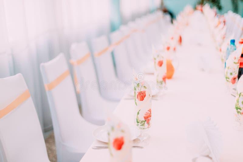 Dekorativa vitansvar och kulöra band på stolar på den festliga tabellen arkivbilder