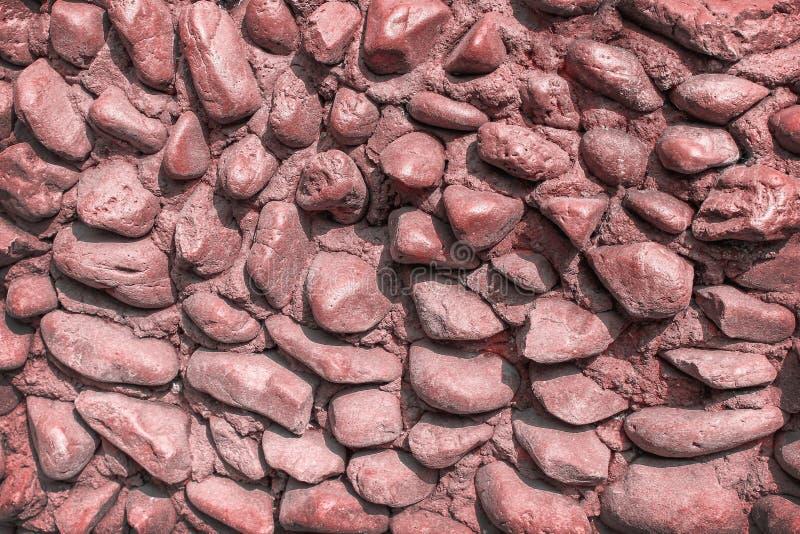 Dekorative alte rote Steinmusterbeschaffenheit der bunten Natur auf Betonmauerhintergrund stockfoto