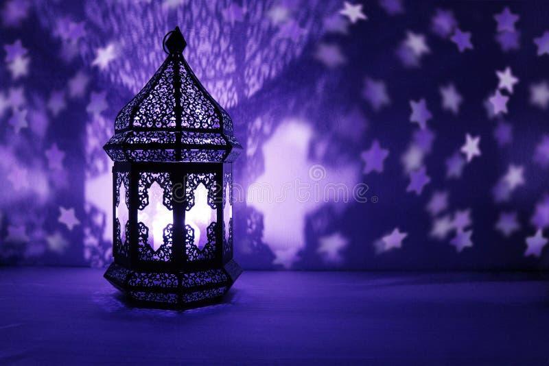 Dekorative arabische Laterne mit der brennenden Kerze glühend nachts und funkelnd spielt geformte bokeh Lichter die Hauptrolle fe lizenzfreie stockfotos