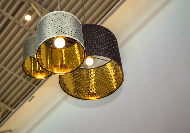 Dekorative Bronzelampen der modernen Art und goldene Lampenschirme hängen an einem langen Seil, industrielle Decke, Innenarchitek stockfotos