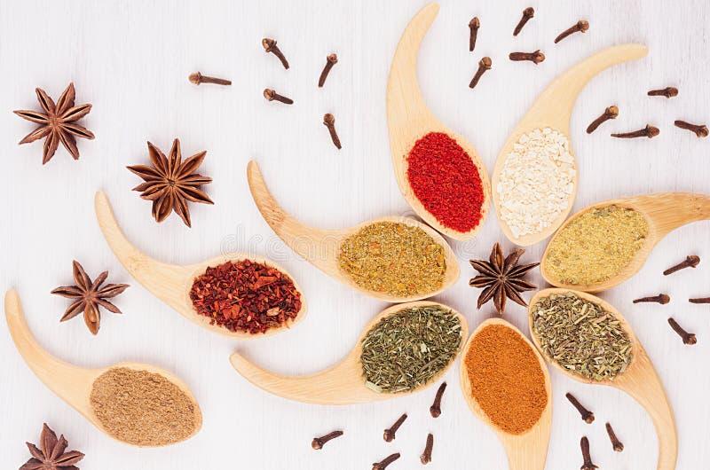 Dekorative bunte Spaßverzierung von mehrfarbigen asiatischen Gewürzen und Anis spielen, Nelke auf weißem hölzernem Hintergrund di stockbild