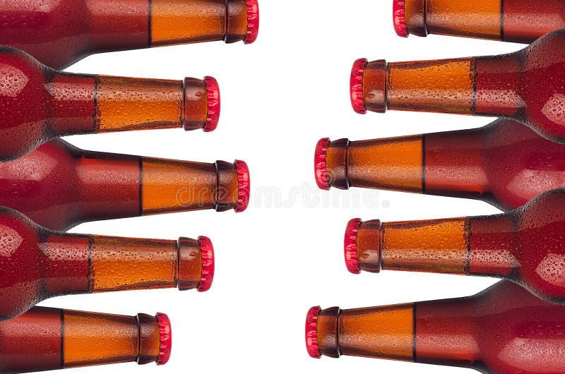 Dekorative Grenze von den kalten roten AleSiegelbierflaschen mit Wassertropfen lokalisiert auf weißem Hintergrund stockfotografie