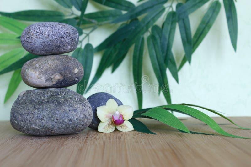 Dekorative Kiesel gestapelt auf eine Zenlebenmode auf einem hölzernen Bambusbrett und einer Orchidee auf einem Grün und einem Lau lizenzfreies stockbild