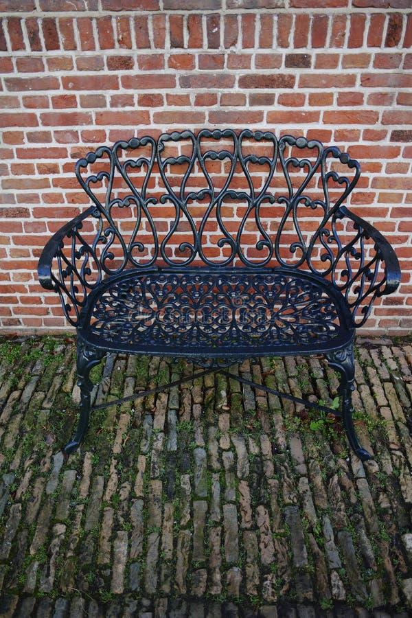 Dekorative Schmiedeeisenbank im Garten lizenzfreie stockfotografie