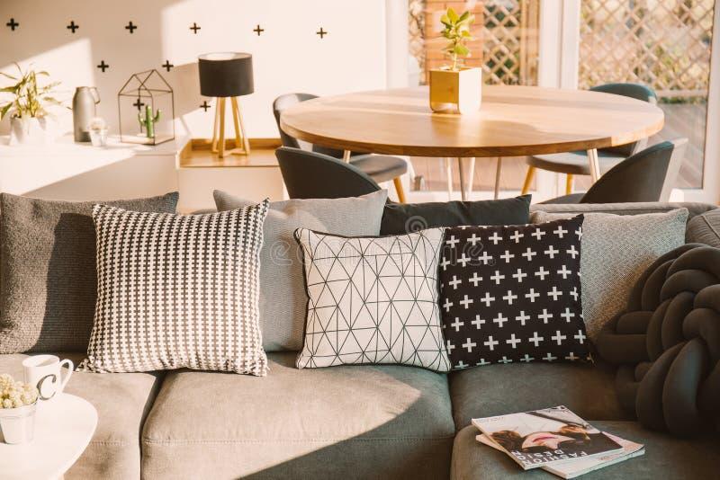 Dekorative Schwarzweiss-Kissen auf einem grauen Sofa in einem sonnenbeschienen Li lizenzfreies stockfoto