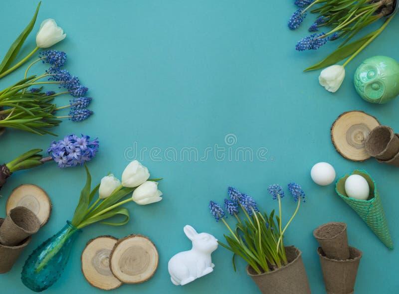 Dekorative Zusammensetzung Ostern auf einem blauen Hintergrund Weiße Tulpen, Blumentöpfe, unbemalte Eier und ein Baum stockfotografie
