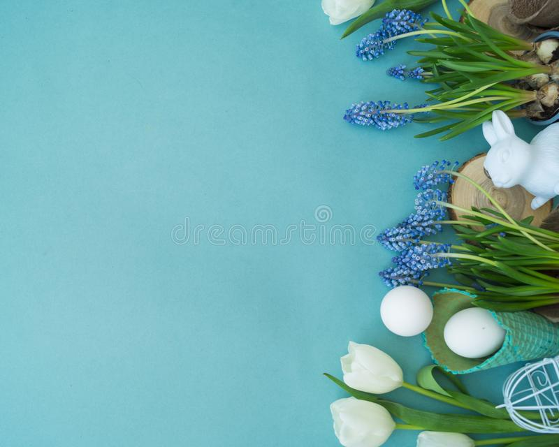 Dekorative Zusammensetzung Ostern auf einem blauen Hintergrund Weißes Kaninchen, Tulpen, Blumentöpfe, unbemalte Eier und ein Baum lizenzfreies stockfoto