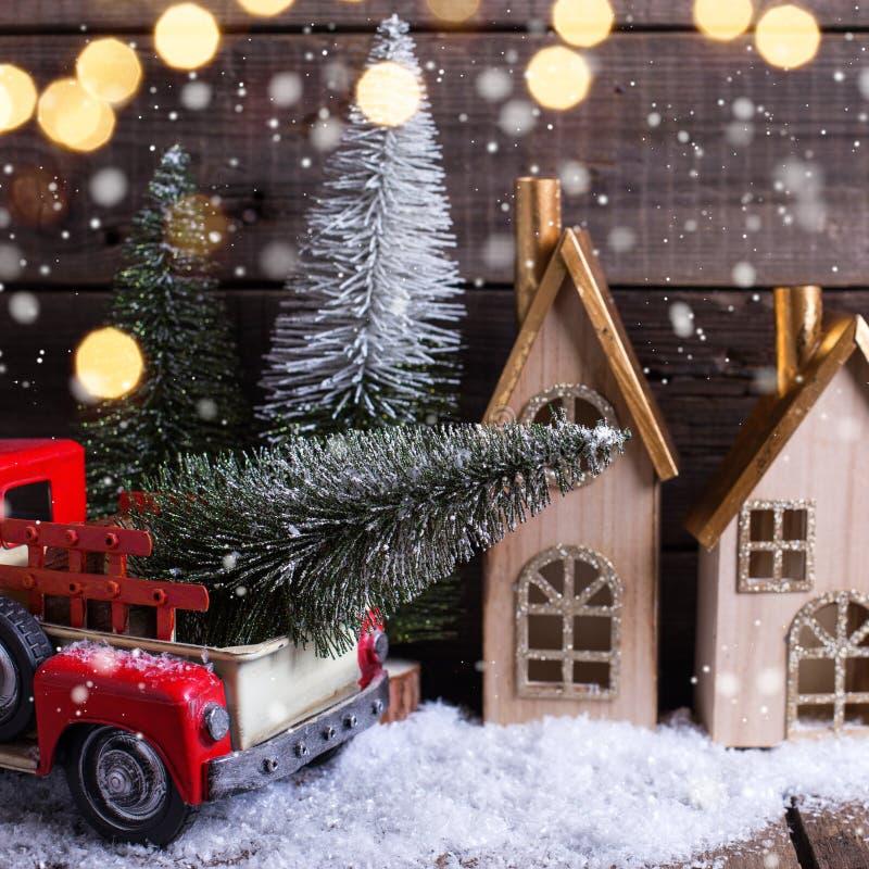 Dekorativer Baum im roten Auto, in den Häusern und in den Pelzbäumen auf gealtertem Holz lizenzfreie stockfotos