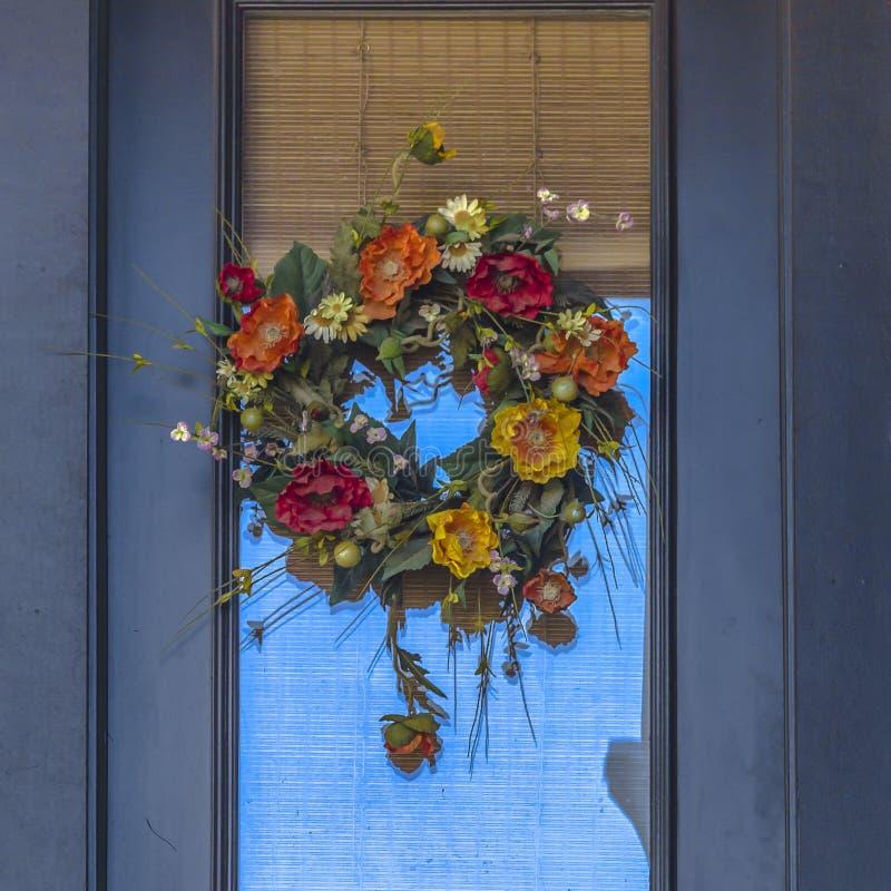 Dekorativer Blumenkranz, der an einer Tür hängt stockfotografie