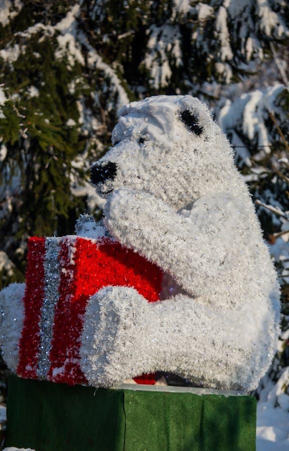 Dekorativer Eisbär mit Reflexion und roter Kasten als Geschenk in t lizenzfreies stockbild