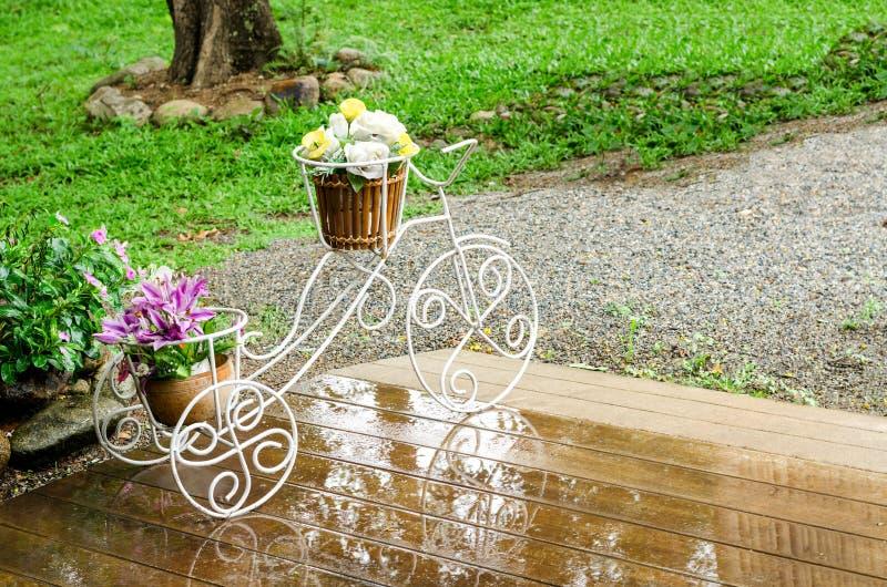 Dekorativer Fahrradvase mit gefälschten Blumen Garten im im Freien stockfoto