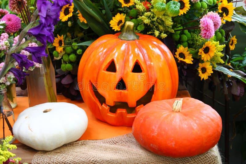 Dekorativer Kürbis Halloweens mit wirklichen Kürbisen und Blumen im Hintergrund stockbild