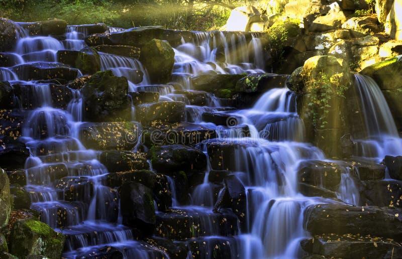 Dekorativer Kaskadenwasserfall mit sichtbarer Sonne strahlt - Virginia Water, Surrey, Vereinigtes Königreich aus lizenzfreie stockfotos