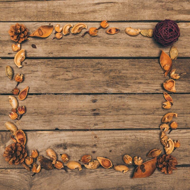 Dekorativer Rahmen gemacht von den trockenen Kegeln, von den Blumen und von den Samen auf rustikalem Holztisch lizenzfreies stockbild