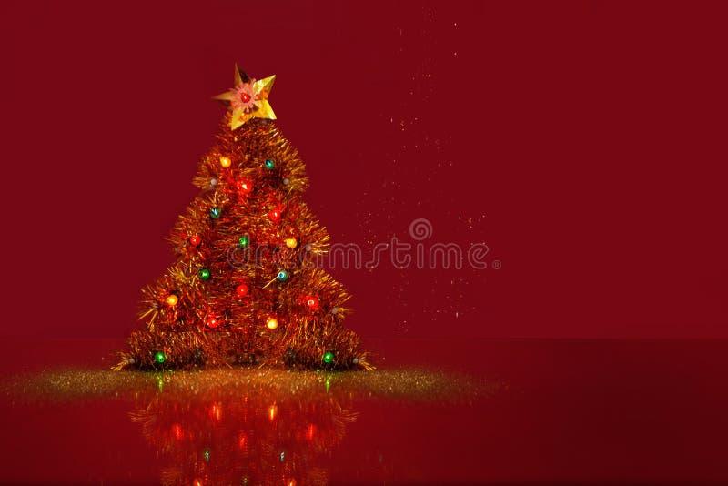 Dekorativer Weihnachtsbaum mit einer glänzenden kleinen Glühlampe Roter Hintergrund mit einem Raum für Text Neues Jahr `s Konzept stockbild