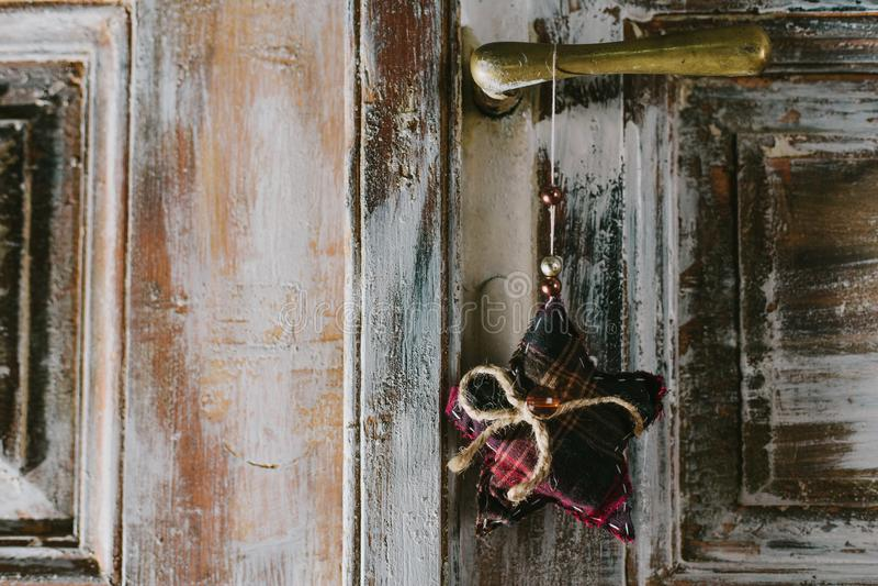 Dekorativer Weihnachtsstern, der am alten Türgriff hängt stockfotos
