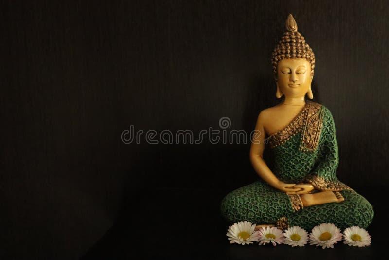 Dekoratives Bild von Buddha über dunklem Hintergrund, mit einigen gelben und weißen Blumen lizenzfreie stockfotografie