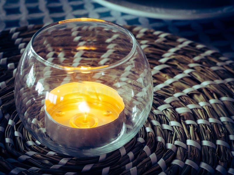 Dekoratives Glas mit einem brennenden Kerzeninnere stockbild