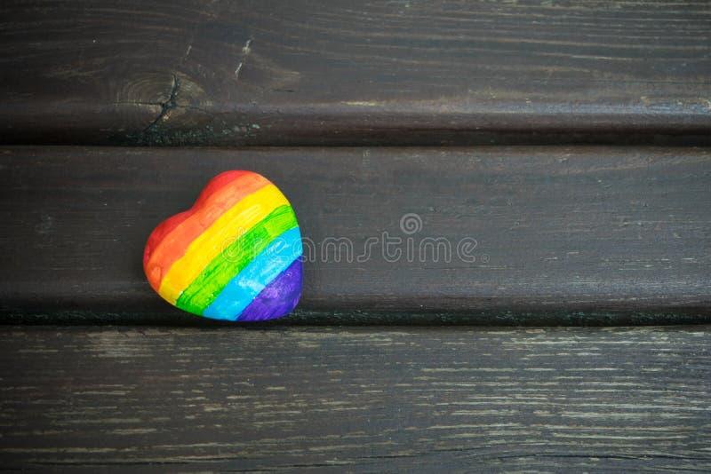 Dekoratives Herz mit Regenbogenstreifen auf dunklem hölzernem Hintergrund LGBT-Stolzflagge, Symbol von lesbischem, homosexuell, b lizenzfreie stockbilder