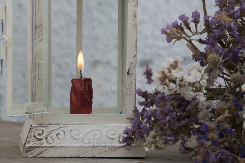 Dekoratives metallisches Laterneninnere, das die Kerze brennt, mit Blumen stockfotografie