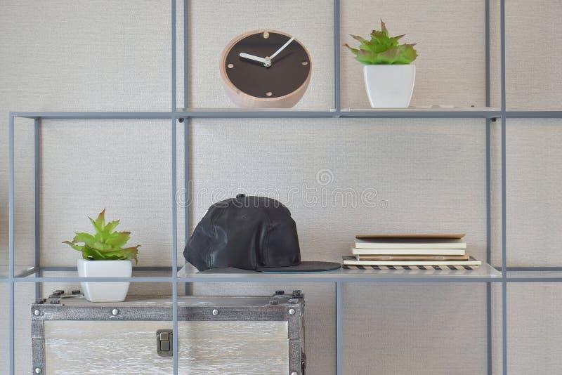 Dekoratives Regal auf Wand mit Büchern, schwarze Kappen, hölzerne Uhr stockfoto