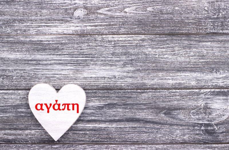 Dekoratives weißes hölzernes Herz auf grauem hölzernem Hintergrund mit Beschriftung Liebe auf Griechisch lizenzfreies stockfoto