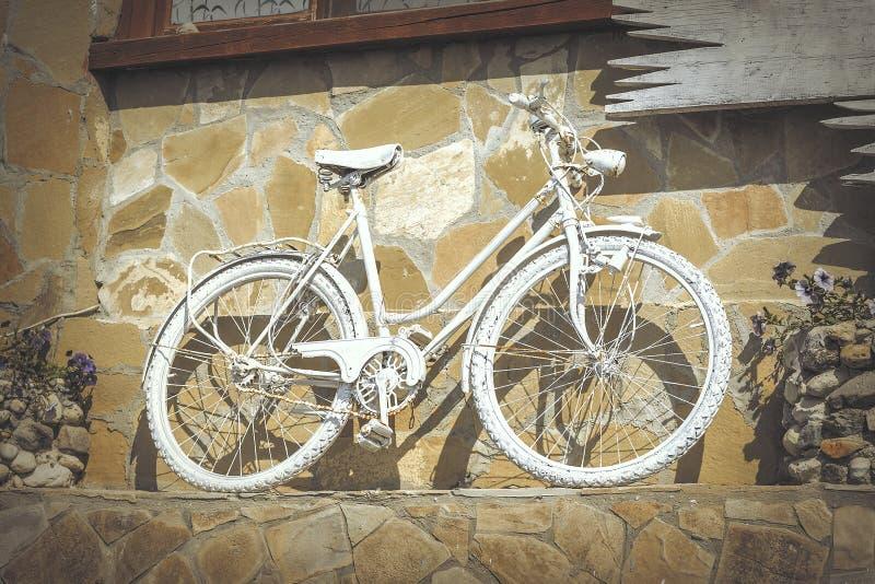 Dekoratives weißes Retro- Fahrrad in der Wand des Gebäudes lizenzfreie stockfotografie