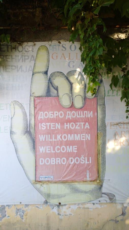 Dekoratives Zeichenwillkommen in den verschiedenen Sprachen in Form einer Hand und eines Zeigefingers stockbilder