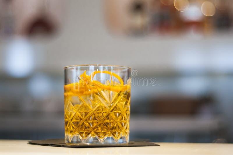Dekorativt exponeringsglas med den orange drinken och apelsinskal på stången arkivbilder